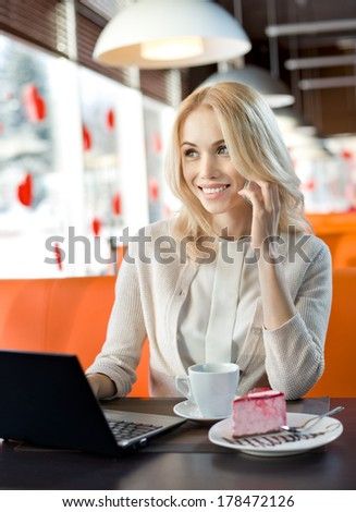 Very beautiful, happy,  young woman, sit in  Cafe and talk on telephone, vertical portrait - stock photo