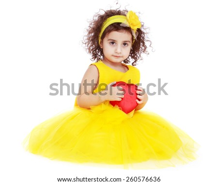 very beautiful little girl in a yellow dress holding a heart - isolated on white. - stock photo