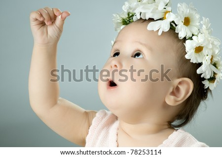 very beautiful  little kid with diadem of flowers, stare , very closeup face - stock photo
