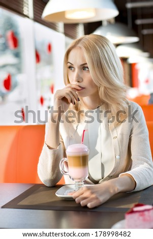 Very beautiful sad young woman, sit in  Cafe and drink coffee- cocktail, vertical portrait
