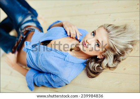 very beautiful, sensual sexy blonde girl with blue eyes in a blue blouse lying on the floor - stock photo