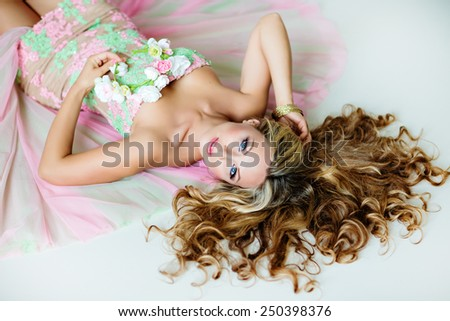 Very beautiful sexy sensual girl with curly blond hair, blue eyes , and with a wreath of delicate spring flowers, lying on white floor - stock photo