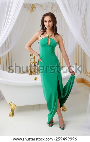 Very beautiful sexy young girl in green dress with big breasts, full lips, slim, athletic build , brunette, in the interior of a bathroom in white and golden tones - stock photo