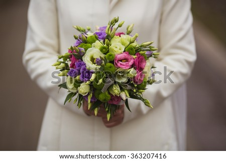 Very beautiful wedding bouquet in the hands of the bride