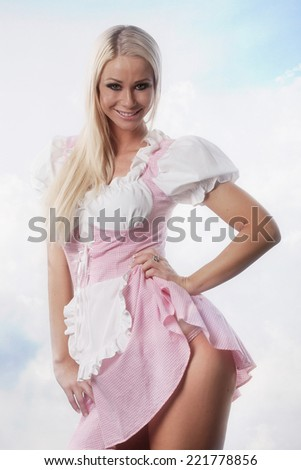 very beautiful woman dressed in oktoberfest dirndl with light clouds background - stock photo
