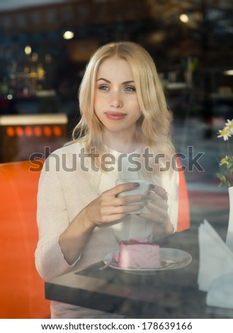 Very beautiful young woman, sit in  Cafe and drink coffee or tea with dessert, street front window view  - stock photo
