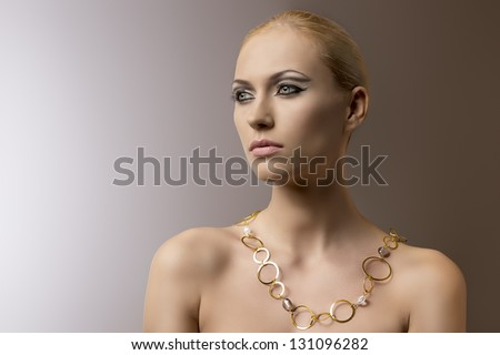 very beauty blonde woman with elegant make-up wearing gold ringed necklace on nude shoulders - stock photo