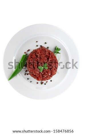 very big raw hamburger cutlet with sprouts and chili pepper on white plate isolated over white background