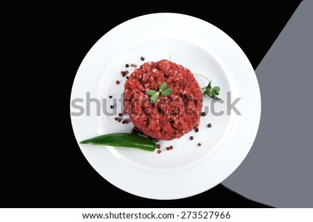 very big raw hamburger cutlet with sprouts and chili pepper on white plate over black background - stock photo