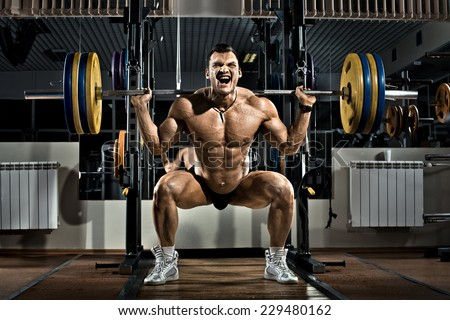 very brawny guy bodybuilder ,  execute exercise squatting with weight, in gym - stock photo