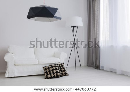 Very bright room arranged in black and white, with a comfortable sofa and decorative pillows - stock photo