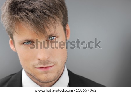 Very close detailed portrait of young man slightly smiling - stock photo