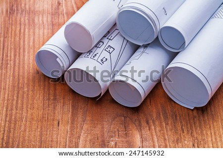 very close up view on stack of blueprints on old wooden board - stock photo