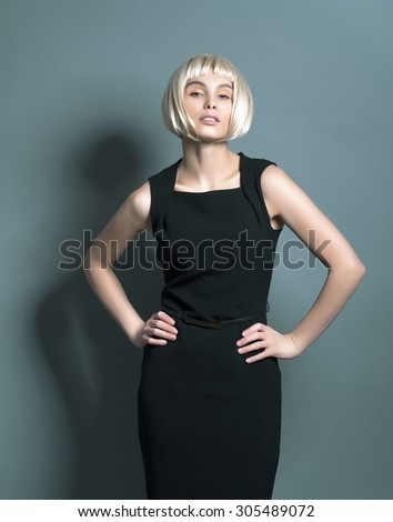 very confident Beautiful young blonde woman in a strict black dress in the studio with short hair and threw her head up holding hands on hips - stock photo