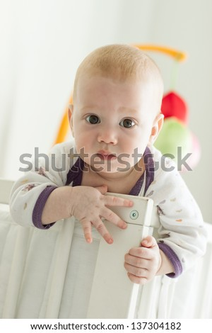 Very curious baby boy peeking out of his crib - stock photo