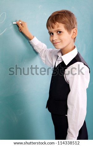 Very cute and positive student is smiling and writing on school blackboard