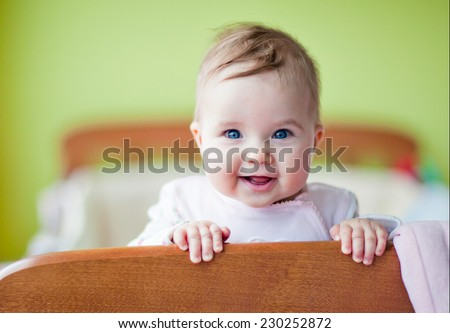 Very cute baby smiles standing in the crib - stock photo