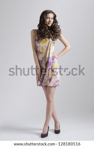 very cute girl with long wavy hair standing on gray background wearing spring dress - stock photo