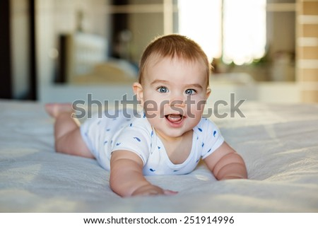 Very cute little baby boy lying on the bed, smiles and fun - stock photo