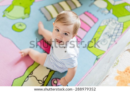 Very cute little blond boy in a striped bodykit sits on the colored carpet and smiling