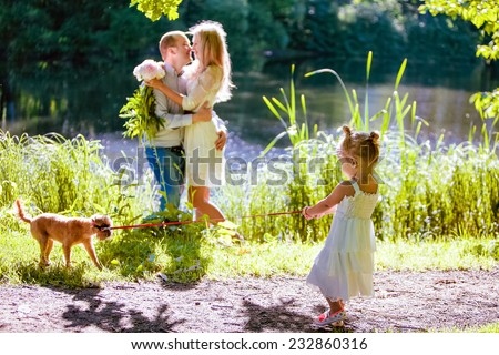 very cute little blonde girl pulls the dog by the leash on the background hugging parents - stock photo