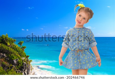 very cute little girl in a blue dress on a sea beach.holiday at the seaside,active lifestyle,happiness concept,carefree childhood concept. - stock photo