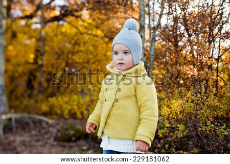 Very cute little girl in a yellow jacket in autumn