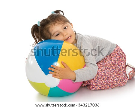 Very cute little girl with pigtails on his head hugging a large ball - Isolated on white background - stock photo