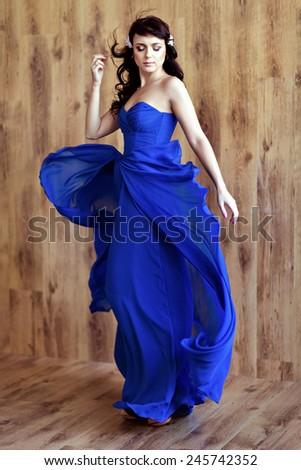 Very cute sensual beautiful girl brunette in blue flowing dress - stock photo