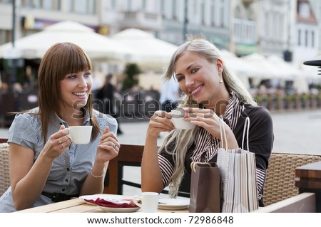 very cute smiling women drinking a coffee sitting outside in a cafe bistro - stock photo