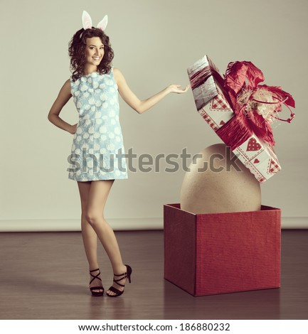 very cute young woman in spring ligh blue dress, with easter bunny ears ,near a big box with egg inside - stock photo