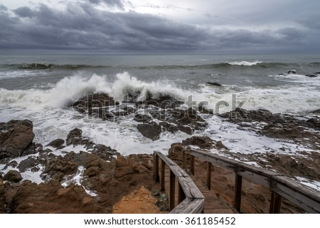 Very dark stormy overcast day El Nino weather storm floods Central California Coast beach, with powerful wind, rain, waves, & heavy surf. Beach access stairs, washed out, near Cambria, CA. - stock photo