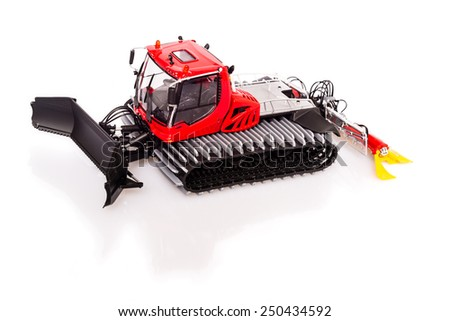 Very detailed toy model of a now-grooming machine or snowcat with reflection and shadow on white background - stock photo