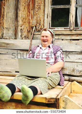 Very elderly woman happily holding a laptop - stock photo