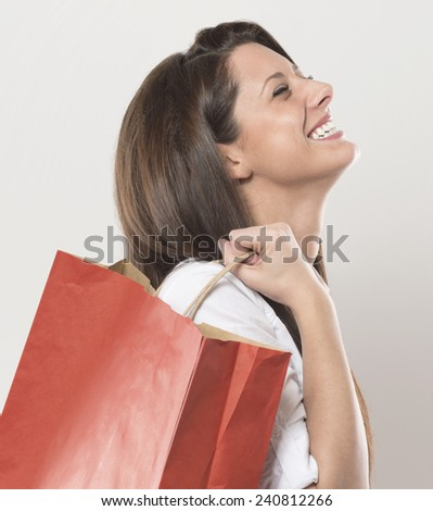 very emotional smiling girl with red shopping bag. studio shot on gray background. - stock photo