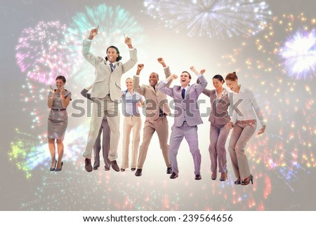 Very enthusiast business people jumping and raising their arms against colourful fireworks exploding on black background - stock photo