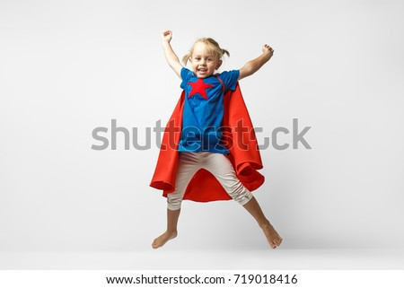 Very excited little girl dressed like hero jumping alongside the white wall.