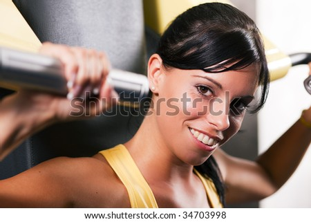 Very fit and beautiful young woman in a gym working out and lifting weights on an exercising machine - stock photo