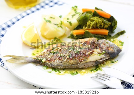 very fresh seabream fish grilled with turnip greens - traditional food from Portugal - stock photo