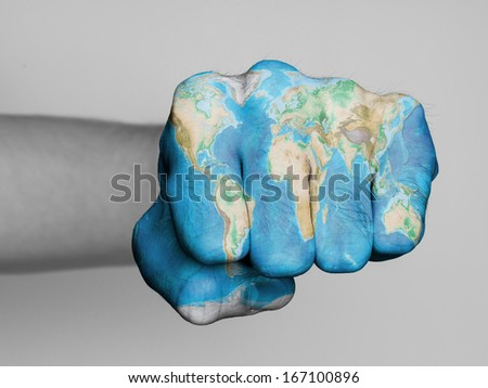 Very hairy knuckles from the fist of a man punching, world map print - stock photo