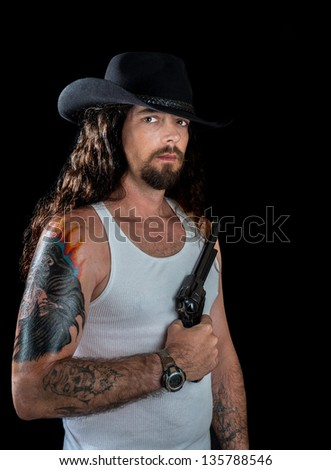 very handsome sexy man with long wavy brown hair and striking eyes wearing a black cowboy hat holding a revolver - stock photo