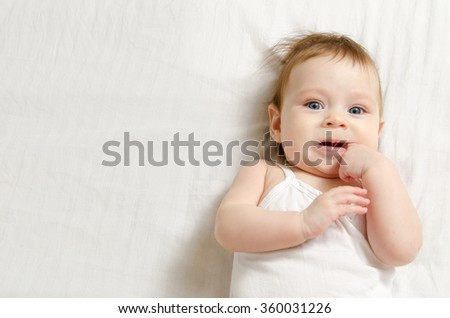 Very happy baby in white body suit lying on his back on the white sheet and sucking his finger.  - stock photo
