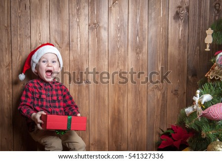 Very happy cute Boy with xmas gifts on wooden background. Child in ...