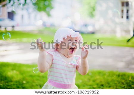 very happy laughing girl playing with soap bubbles - stock photo