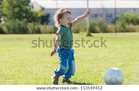 very happy little boy playing with ball on football field