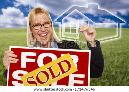 Very Happy Woman with Sold For Sale Real Estate Sign, Keys In Hand and Ghosted House Behind Her. - stock photo