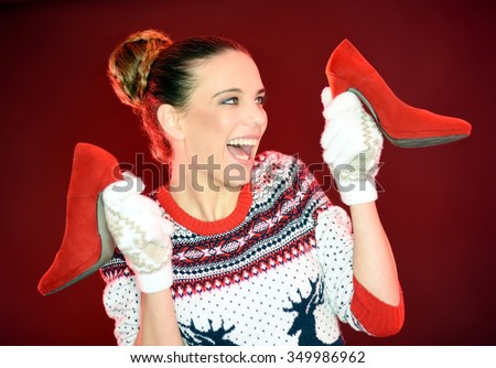 Very happy young girl celebrates Christmas with a big smile on her Christmas gift. Smiling woman with Christmas gloves holding  a pair of red high heels shoes. - stock photo