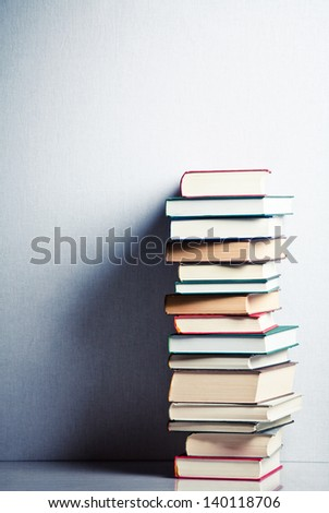 Very high stack of books on a table