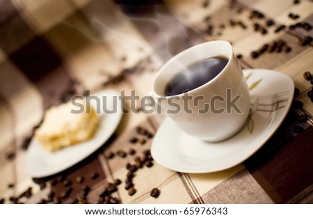 Very hot coffee in cup and cake on table, cake in blurred background - stock photo