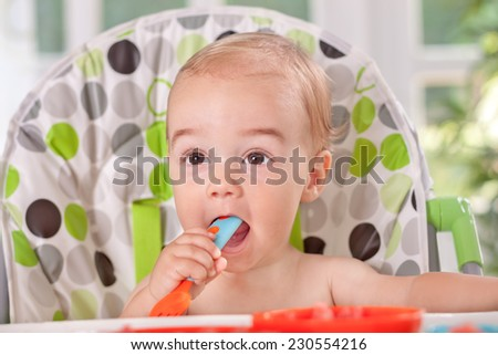 Very hungry baby with cutlery - stock photo